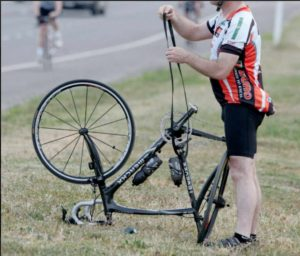 a cyclist repairs the back tire of his bike