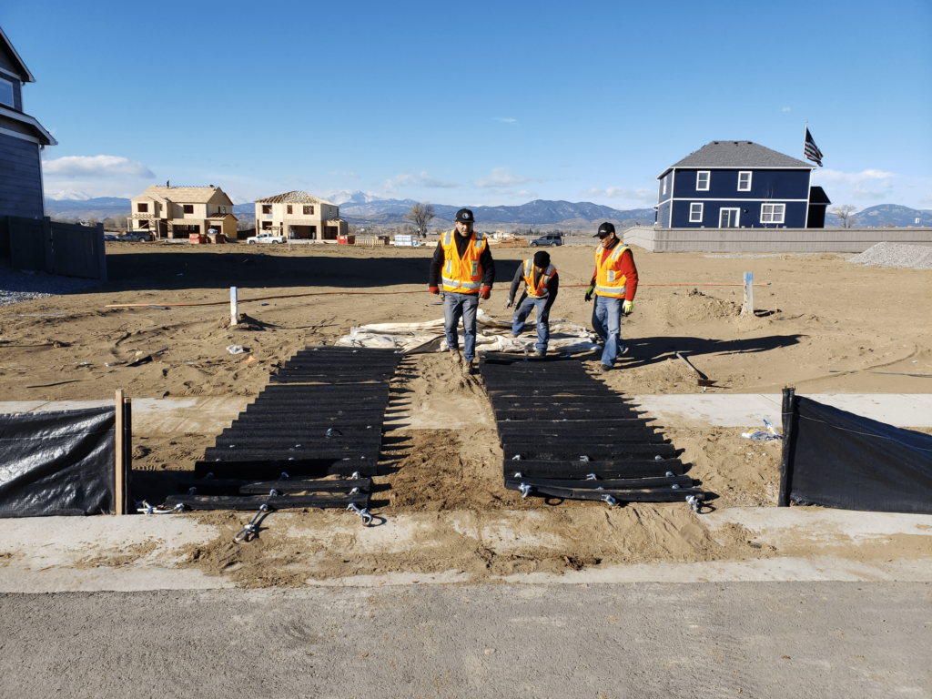 Three men installing a Renegade Rumble Strip in a residential development